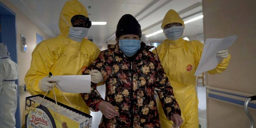 "Two people in hazmat suits escort a patient in the documentary ""76 Days."""