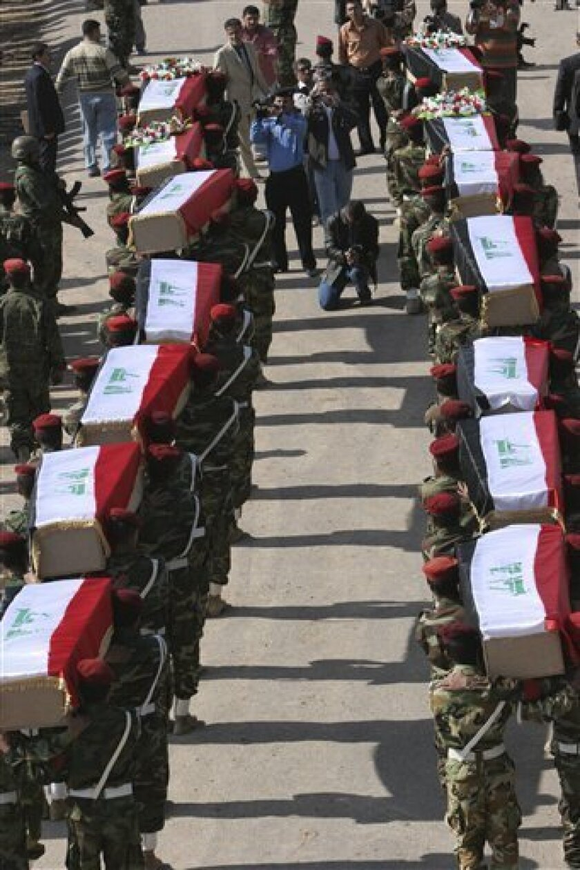 Iraqi soldiers carry coffins with the remains of Iraqi soldiers killed during an eight-year war between Iran and Iraq at the border crossing  of Al-Shalamjah, Iraq, Sunday, Nov. 30, 2008. The remains of 200 Iraqis and 41 Iranians were returned to their native countries Sunday during a ceremony at a