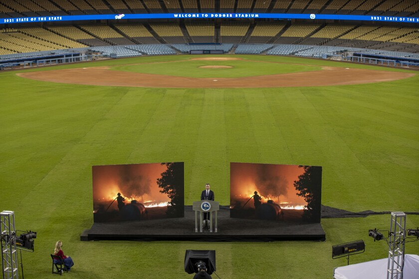 Newsom speaking from Dodger Stadium with TV screens showing images of fires behind him