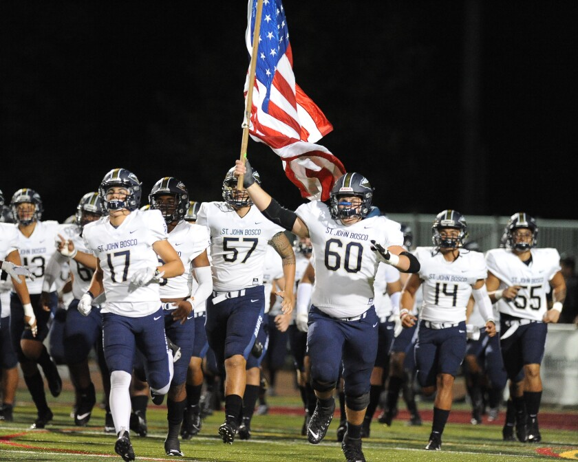 St. John Bosco left tackle Drake Metcalf (60) leads the Braves onto the field for a game earlier this season.