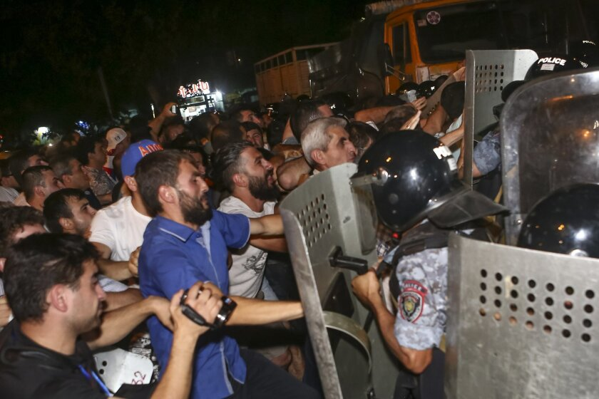 Armenian protesters clash with police officers near the area around a police station in Yerevan, Armenia, Wednesday, July 20, 2016.  Demonstrators and police have clashed outside a police station in the Armenian capital where armed supporters of a jailed opposition leader have held hostages for fou