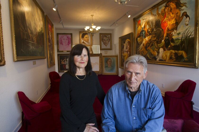 Siblings Barry and Lynn Baron stand with some of the works painted by their deceased sister Noel.