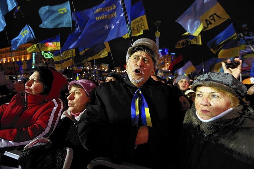Ukrainians gathered in Kiev's Independence Square demand President Viktor Yanukovich's resignation after he reached agreement with Russia for a $15-billion loan and a more than 30% cut in the price of Russian natural gas. The deal would draw Ukraine deeper into Moscow's sphere.