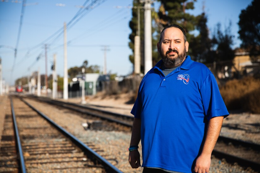 Rudy Lopez stands on train tracks at San Ysidro