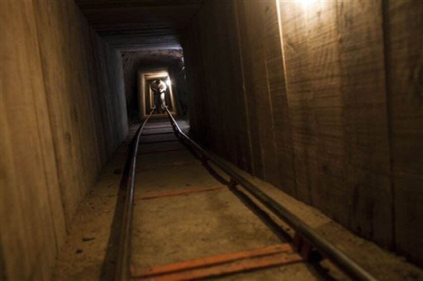 A news photographer walks inside a tunnel in the northern border city  of Tijuana, Mexico Wednesday Nov. 30, 2011. A day earlier, the tunnel was discovered by U.S. authorities in San Diego's Otay Mesa area, the latest in a spate of secret passages found to smuggle drugs from Mexico.  This tunnel
