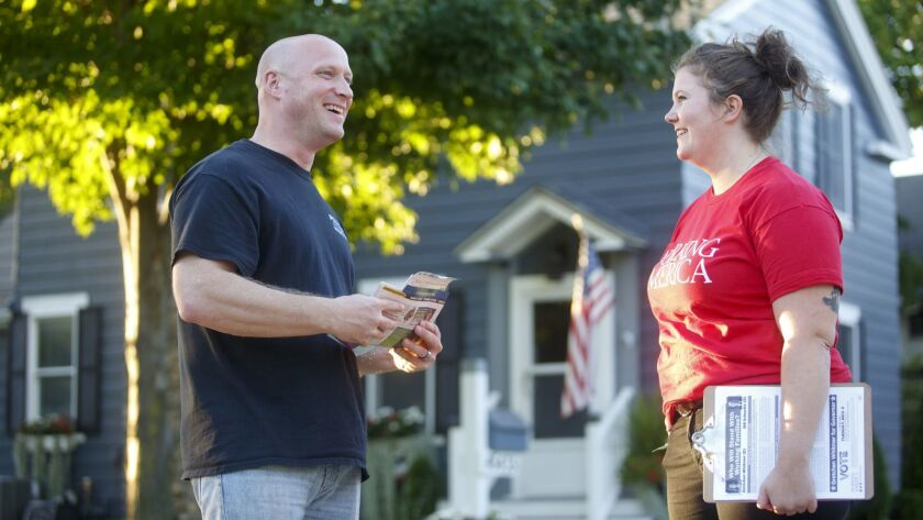 Thom Dionne, 45, left, speaks to Working America canvasser Jaclyn McCann, 28, in Utica, Mich., on Oct. 4. Dionne is a police officer and mayor.