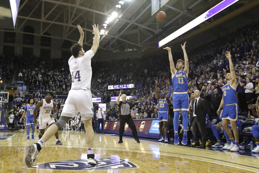 UCLA's Jake Kyman puts up a three-point shot with seconds left as Washington's Sam Timmins (14) is late to defend the shot on  Jan. 2 in Seattle