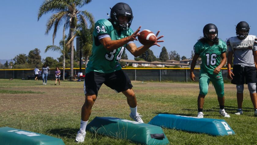 Hilltop's Oscar Piceno catches a pass while running a sidestepping drill at practice on Monday.