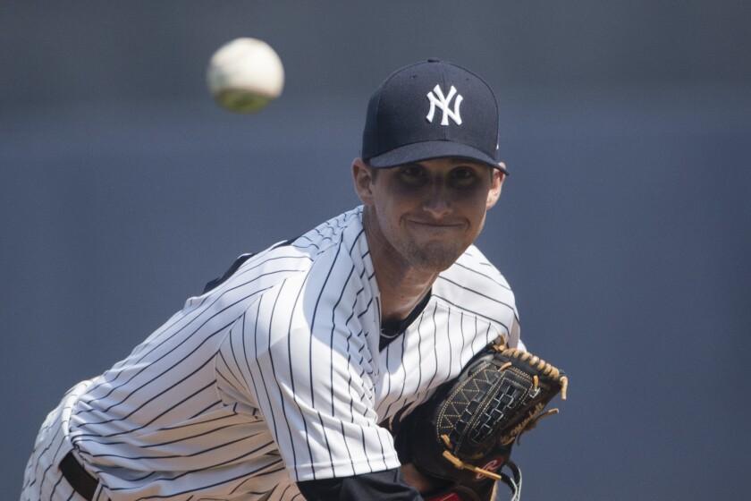New York Yankees starting pitcher Bryan Mitchell warms up during a spring training baseball game aga