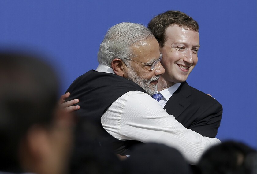 FILE - In this Sept. 27, 2015, file photo, Facebook CEO Mark Zuckerberg, right, hugs Prime Minister of India Narendra Modi at Facebook in Menlo Park, Calif. Members of India's governing party on Monday rejected allegations that Facebook had chosen to turn a blind eye to partisan hate speech on its platform to protect its growing business interests in India. As usage has spread across India, Facebook and its subsidiary WhatsApp have become fierce battlegrounds for India's political parties, but spokesmen for Prime Minister Narendra Modi's Bharatiya Janata Party denied a newspaper report that asserted Facebook officials chose not to take action against party members whose posts violated rules against hate speech. (AP Photo/Jeff Chiu, File)