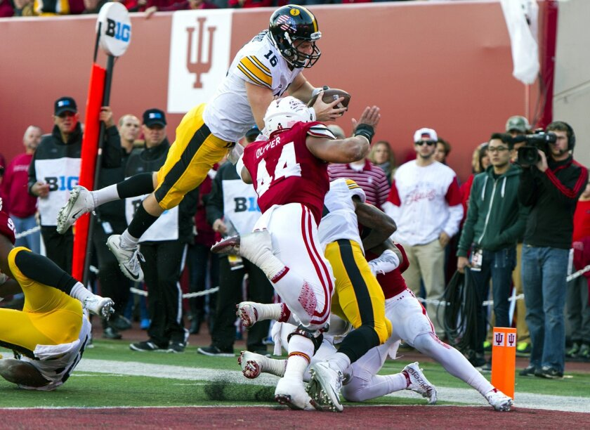 Iowa quarterback C.J. Beathard (16) dives over the Indiana defense to score during the first half of an NCAA college football game in Bloomington, Ind., Saturday, Nov. 7, 2015. (AP Photo/Doug McSchooler)