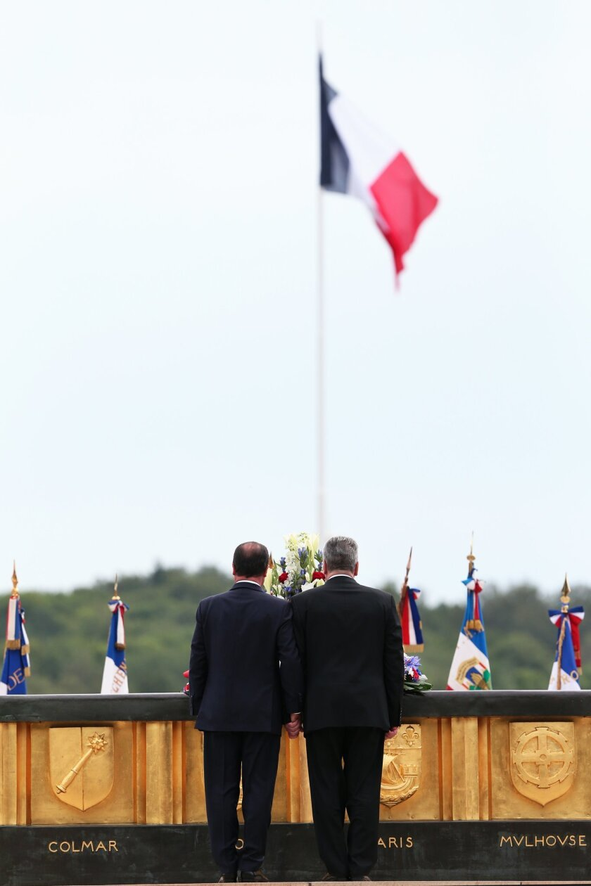 France's President Francois Hollande, left, and German President Joachim Gauck pay respect during a ceremony to mark the 100th anniversary of the outbreak of World War I, at the National Monument of Hartmannswillerkop, in Wattwiller, eastern France, Sunday, Aug. 3, 2014. On this day 100-years ago, in 1914, Germany declared war on France, at the beginning of the first global war, which centered on Europe and resulted in over nine million combatants being killed. (AP Photo/Thibault Camus)