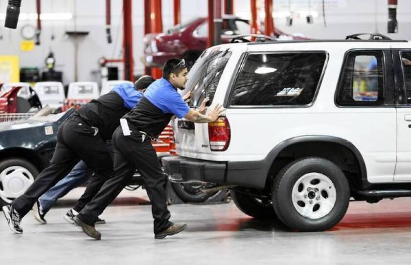 Corinthian Colleges enroll about 81,000 students at 111 schools in 25 states and Canada. Above, students push a Ford Explorer during an automotive technology class at WyoTech in Long Beach in 2011.
