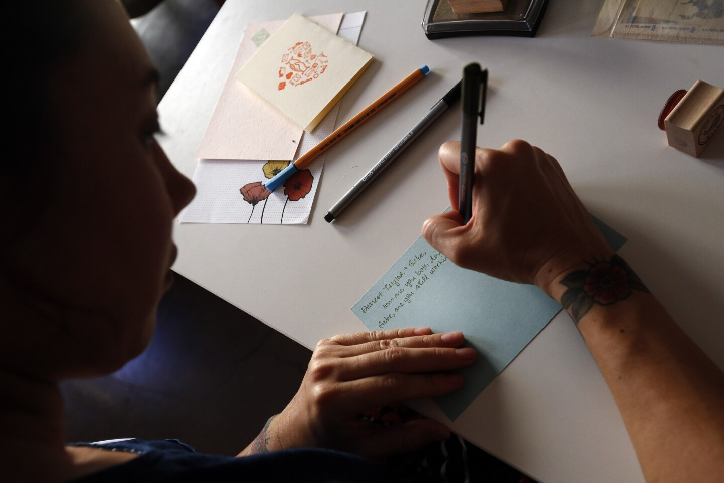 Erika Mulan writes a letter to a pen pal in Atlanta during the monthly gathering of the L.A. Pen Pal Club at Paper Pastries Atelier in downtown Los Angeles.