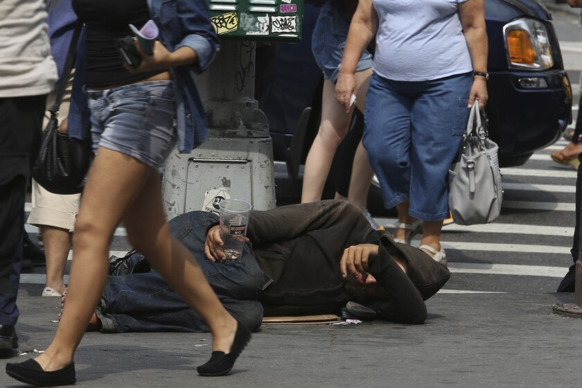 La gente camina junto a un indigente tirado en el suelo que pide dinero en la calle 14 de Nueva York el 4 de septiembre del 2015. Las redes sociales se han convertido en un intrumento para difundir fotos e información de los indigentes, que para muchos son una violación de sus derechos.