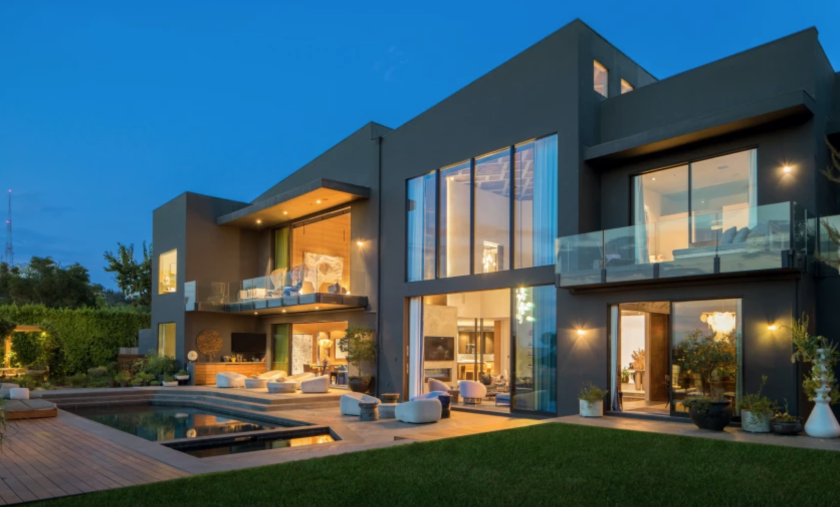 Exterior of a mansion with a lot of floor to ceiling windows and a pol outside.
