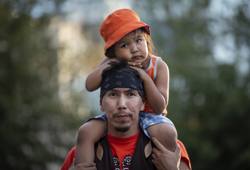 Cowichan Tribe member Benny George holds his child on his shoulders