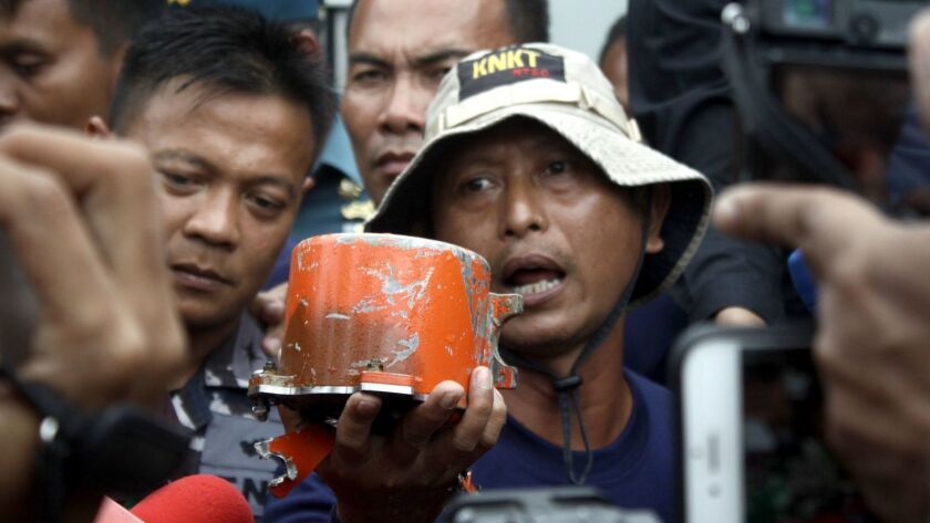 A member of the Indonesian National Commission of Transportation Safety shows the cockpit voice recorder recovered from a Lion Air jet that crashed off Indonesia in 2018.