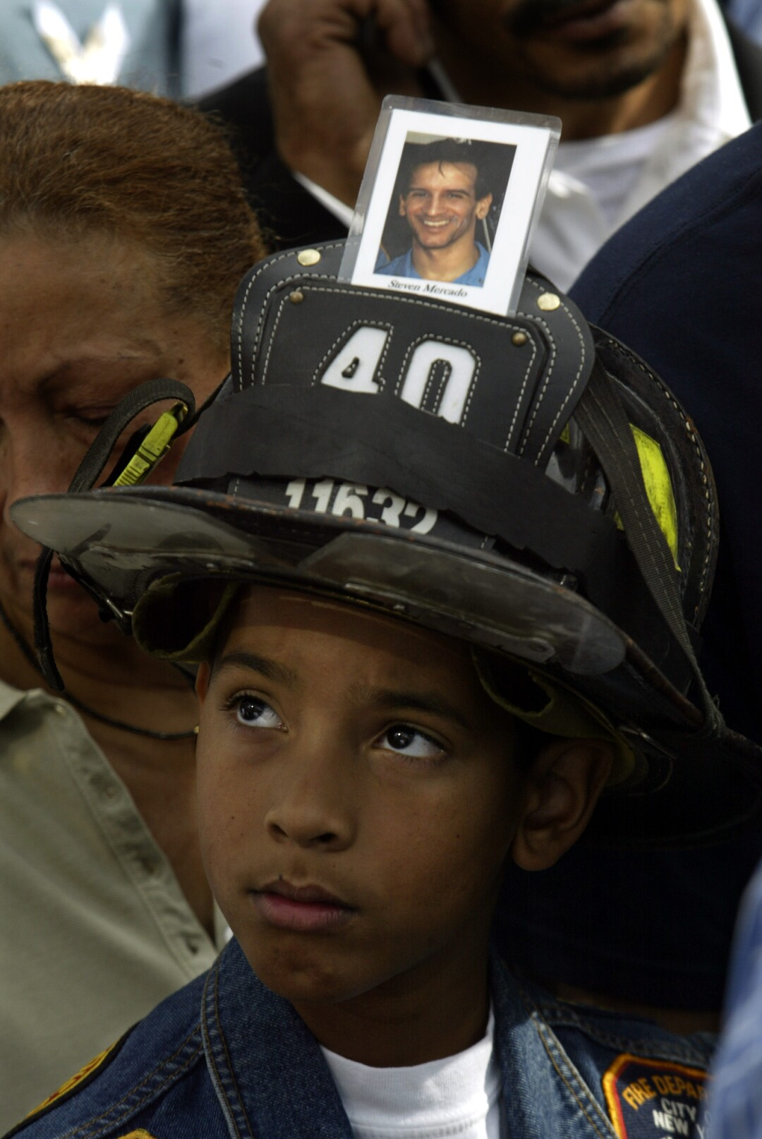 A boy wears a firefighter's helmet with a photo attached