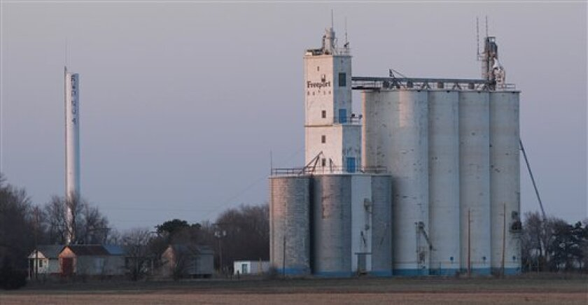 In this Thursday, March 3, 2011 photograph, A grain elevator and water tower are seen from the unsurfaced road to Freeport, Kan. (AP Photo/Orlin Wagner)