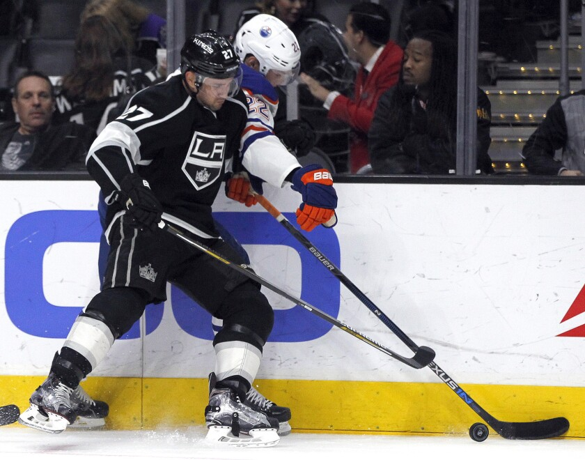 Kings defenseman Alec Martinez, left, pinches Oilers forward Adam Cracknell, right, against the boards during the third period of a game on March 26.