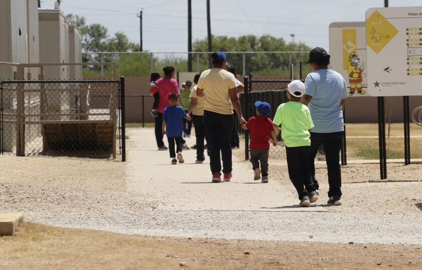 Adults hold hands with children as they walk from a dirt yard onto a sidewalk in a fenced area at an ICE detention center