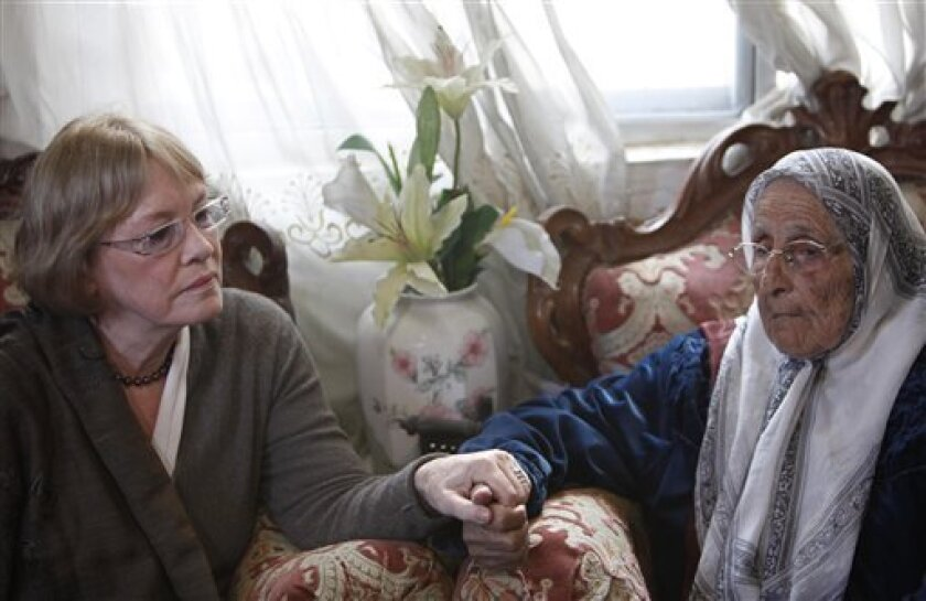 "U.N. Relief and Works Agency (UNRWA) commissioner Karen Abu Zayd, left, holds the hand of Rifka al-Kurd, the grandmother of the family who was evicted last week from a disputed house in the east Jerusalem neighborhood of Sheikh Jarrah, Thursday, Dec. 10, 2009. Abu Zayd called on Israel Thursday to return Palestinians evicted from an east Jerusalem neighborhood to their homes. ""UNRWA calls upon the Israeli authorities to reinstate all Palestine refugee families that have been displaced or forcibly evicted from their homes in Sheikh Jarrah and asks that the dignity, rights and freedoms of these people be protected at all times,"" Abu Zayd said.(AP Photo/ Tara Todras-Whitehill)"
