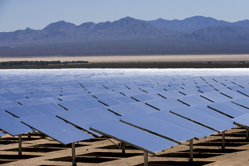Reflective solar panels in the desert with mountains in the background