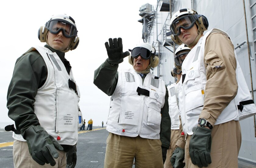 Secretary of Defense Leon Panetta, center, gestures on the flight deck of the Peleliu Friday afternoon. Panetta told hundreds of Marines and sailors that Congress would be putting a gun to America's head if it permits across-the-board military budget cuts.