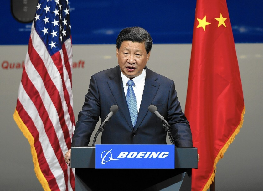 Chinese President Xi Jinping speaks after his tour of the Boeing assembly line in Everett, Wash. In deals signed during his U.S. visit this week, Chinese companies agreed to buy 300 Boeing jets and build the airliner's first assembly plant in China.