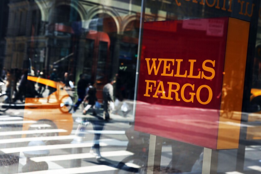 Pedestrians pass a Wells Fargo bank branch in Lower Manhattan on April 15 in New York City.