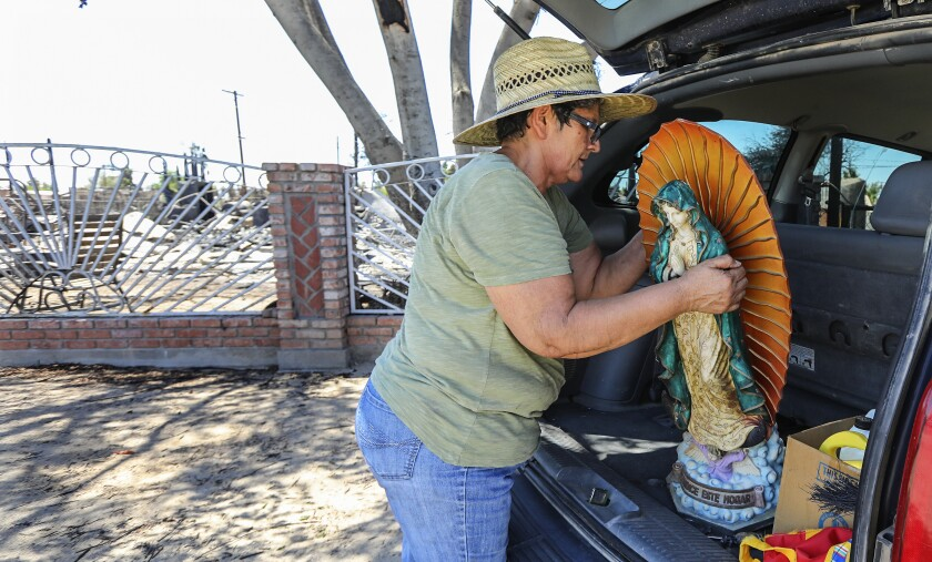 A woman loads a Virgin Mary statue into her car at the charred remains of her home