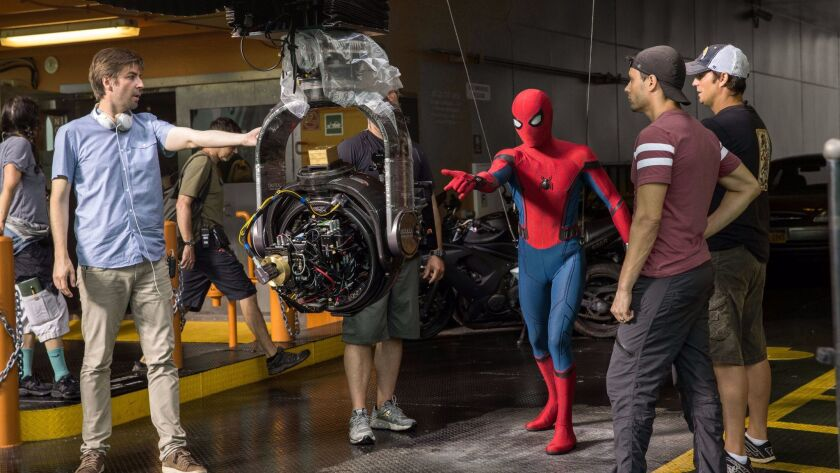 "Director Jon Watts, left, with cast and crew on the set of ""Spider-Man: Homecoming."""