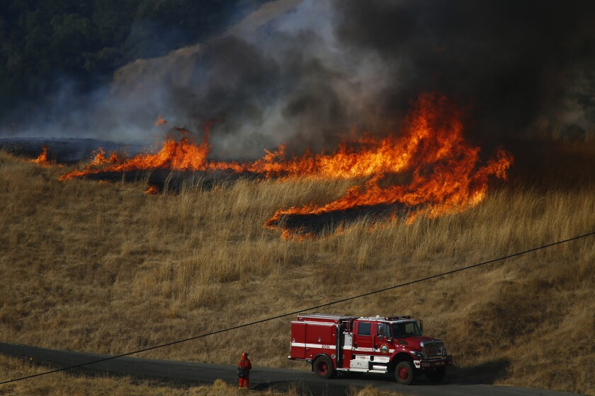 Firefighters monitor a back fire in the hills above Healdsburg, Calif., on Saturday.