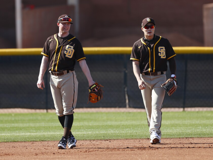 Padres second basemen Jake Cronenworth, left, and Ha-seong Kim work out during spring training drill on Tuesday.