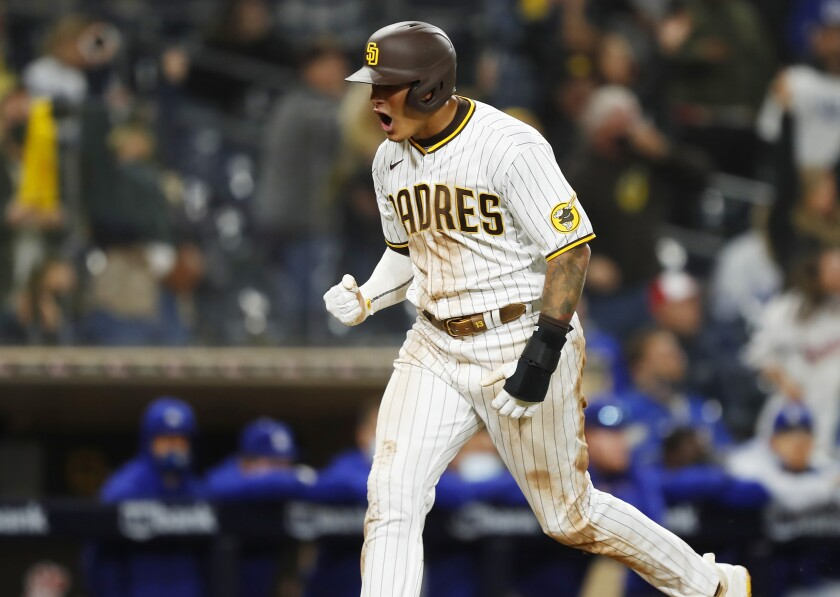 Padres and Manny Machado, shown scoring the tying run in the ninth inning Friday vs. the Dodgers, lost 11-6 in 12 innings.