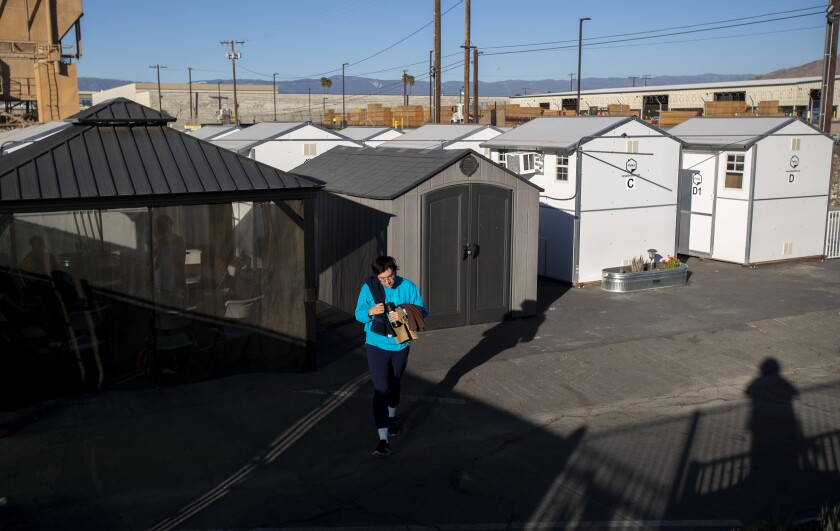 A resident of a  tiny home village in Riverside walks to the common shower area