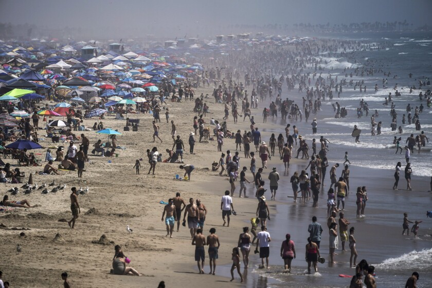 In this Sept. 5, 2020 file photo, people crowd the beach in Huntington Beach, as the state swelters under a heat wave.