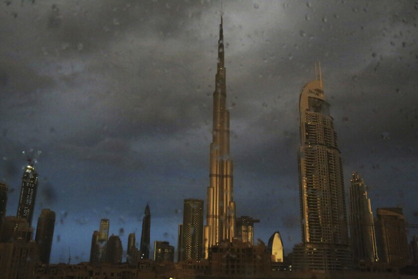FILE - In this Nov. 26, 2018 file photo, sunlight reflects off the Burj Khalifa, the world's tallest building, during a rain shower in Dubai, United Arab Emirates. For eager Israelis, anticipation is mounting that Dubai's glitzy Burj Khalifa, will soon join the ranks of the Pyramids in Egypt and relics of the ancient Nabatean Kingdom of Petra in Jordan as an iconic landmark that was once unattainable but is now within reach. Last week's dramatic announcement making the UAE just the third Arab nation to establish full diplomatic ties with Israel has set off a flurry of excitement. (AP Photo/Jon Gambrell, File)