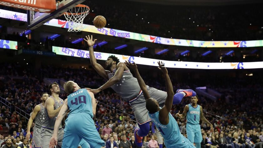 Philadelphia 76ers' Joel Embiid, center, tries to get a shot past Charlotte Hornets' Michael Kidd-Gilchrist, right, and Cody Zeller during the second half.