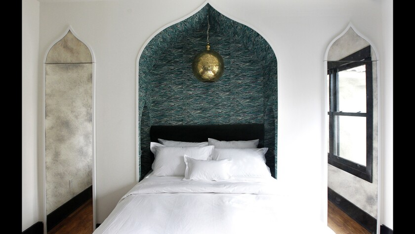 A bedroom in Hotel Covell's Chapter 4 two-bedroom suite features onion dome-shaped niches and handmade marbled wallpaper inspired by George Covell's fictional travels in Morocco and India. The mirrored surfaces that flank the inset bed contain closets.