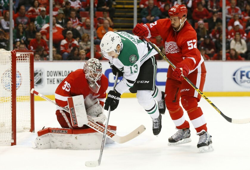 Detroit Red Wings defenseman Jonathan Ericsson (52) checks Dallas Stars center Mattias Janmark (13) as goalie Jimmy Howard (35) stops a shot in the first period of an NHL hockey game, Sunday, Nov. 8, 2015 in Detroit. (AP Photo/Paul Sancya)