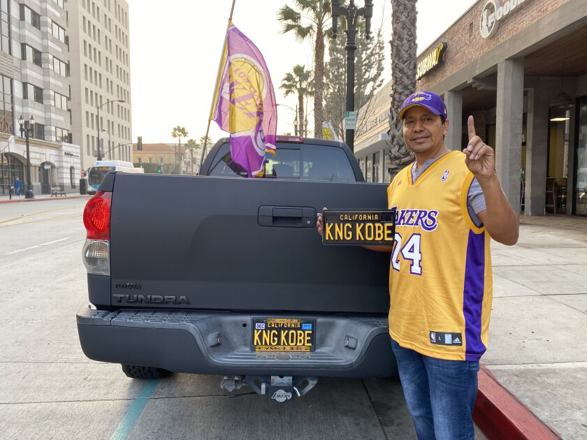 Ron Bonilla stands behind his truck that features a KNG KOBE license plate and a Lakers flag at half-staff.
