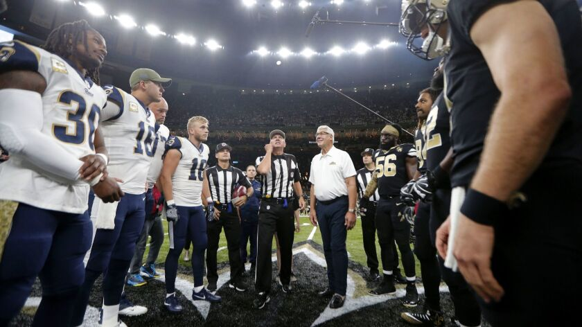 A referee performs the coin toss before an NFL football game between the New Orleans Saints and the