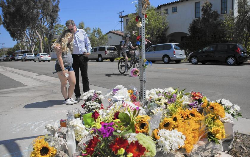Kent Barkouras and daughter Sara visit a memorial at 15th Street and Michael Place in Newport Beach on May 26, 2016, the day after Brock McCann, 8, was struck and killed there by a trash truck.