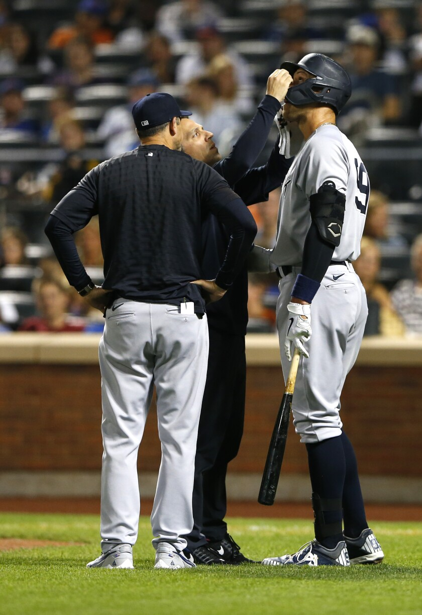 New York Yankees manager Aaron Boone checks on New York Yankees Aaron Judge during a time out against the New York Mets during the first inning of a baseball game on Sunday, Sept.12, 2021, in New York. (AP Photo/Noah K. Murray)