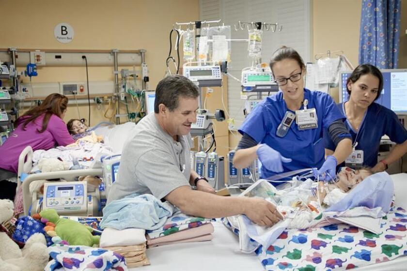 Las hermanas Eva y Erika Sandoval, que hasta hace una semana estaban unidas por su abdomen y compartían órganos vitales, son atendidas por las enfermeras en su habitación del hospital.