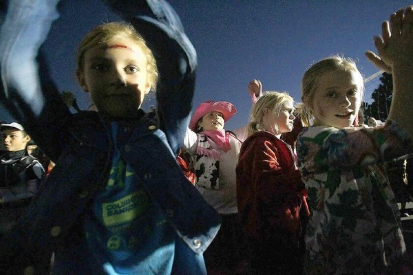 """More than 100 fourth-grade students at Mariners Elementary School perform a flash mob to """"Thriller"""" at the school's Boo Fest on Thursday."""