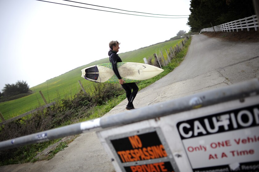 Surfer Mike Wallace of El Granada walks past the gate on the now private road on his way to Martin's Beach in Half Moon Bay last March.