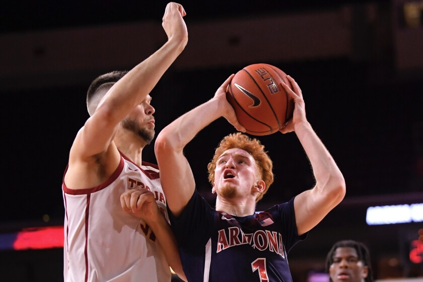Arizona guard Nico Mannion, right, shoots as USC forward Nick Rakocevic defends during the second half on Thursday at Galen Center.